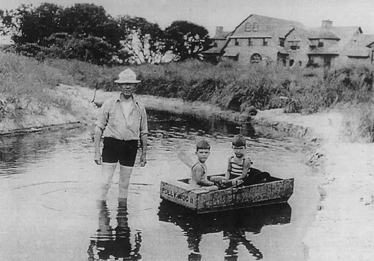Henry C. White teaching his grandsons how to row a boat.