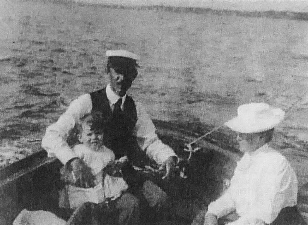 Henry and Grace White sailing with son John in their boat, ca. 1893.
